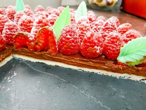 Découpe de la tarte chocolat framboises réalisées par Manon du blog de pâtisserie lesjoliesframboises.com