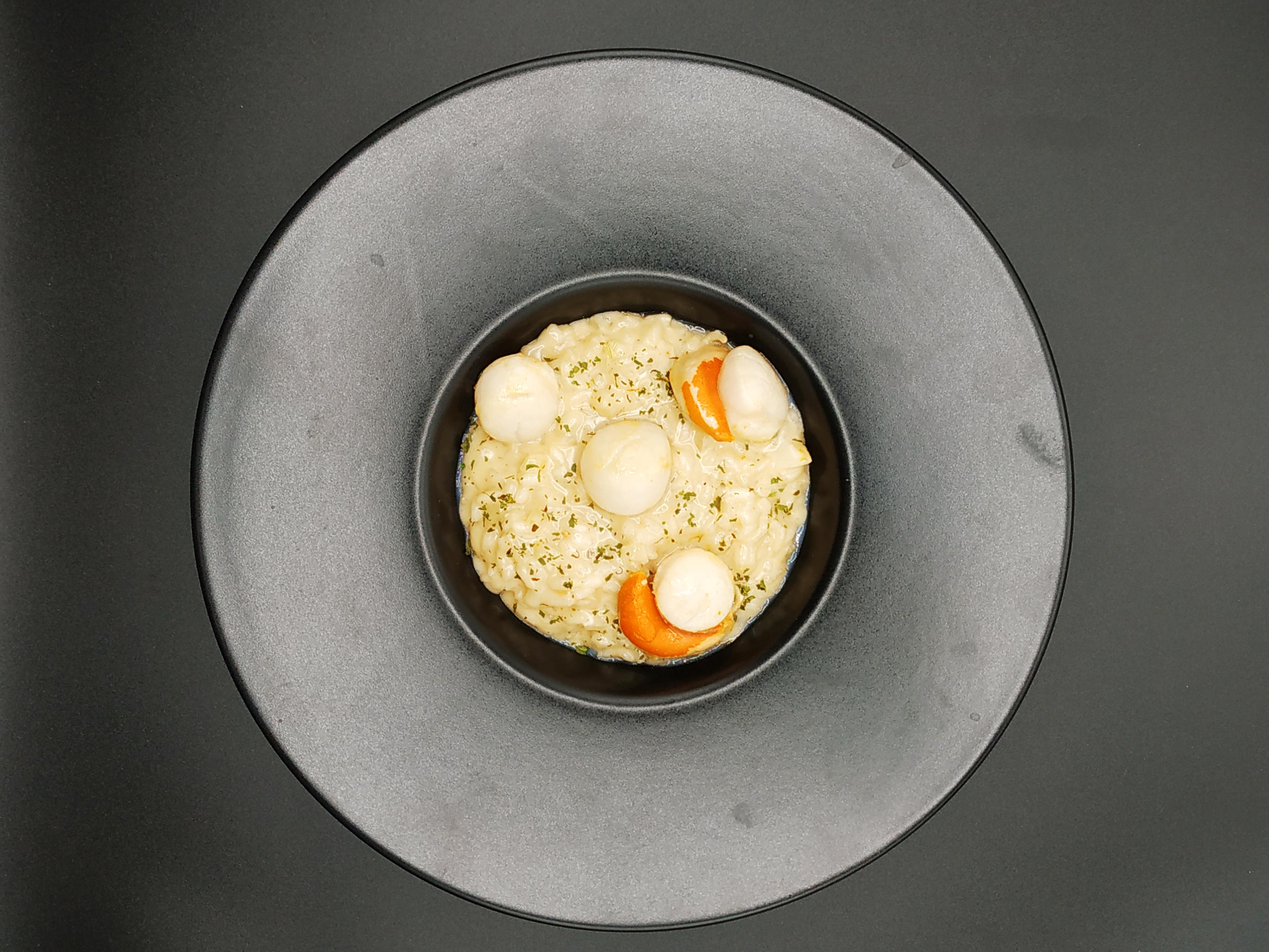 Risotto aux St Jacques et Vin Jaune présenté dans une belle assiette creuse noire